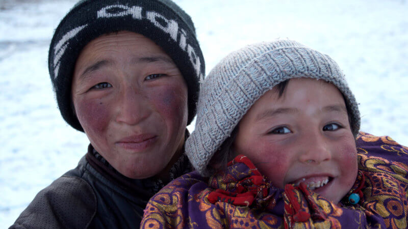 A Kazakh boy lifts up his younger brother for the camera, both playfully smiling.