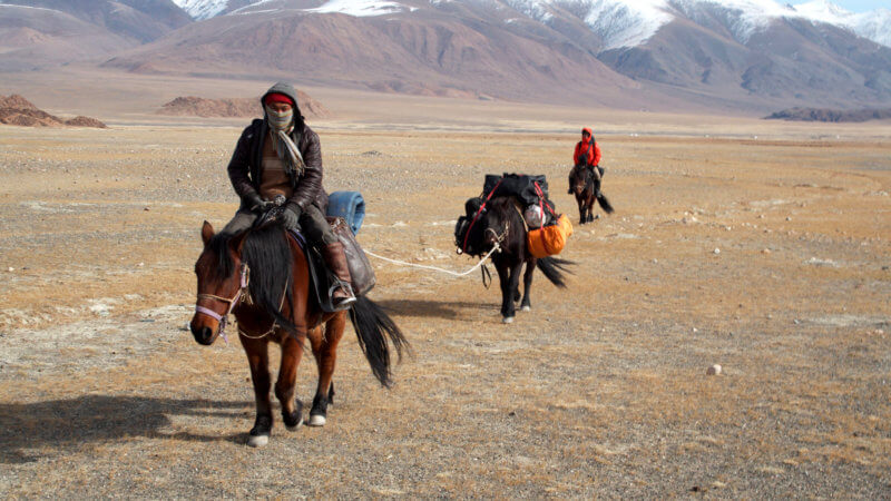 Three horses and two guys loaded with equipment, riding across a flat Mongolian steppe.