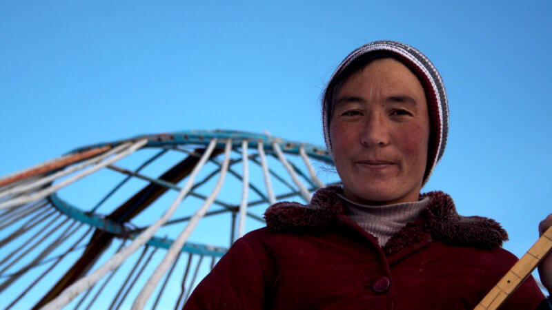 A Kazakh woman holding a dombra instrument, stood in front of her disassembled yurt.