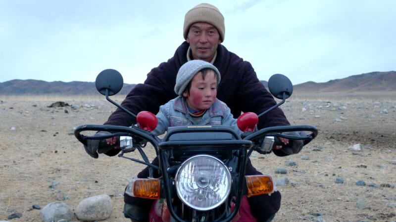 A Kazakh man and his child sat on top of their motorcycle playfully posing for a photo.