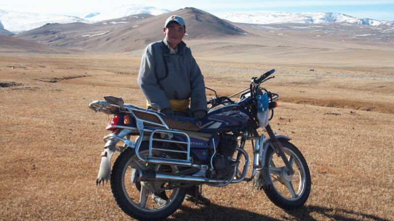 A Mongolian man wearing traditional clothing stood beside his motorcycle.