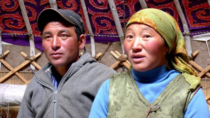 A Kazakh man and woman talking inside of a ger in Western Mongolia.