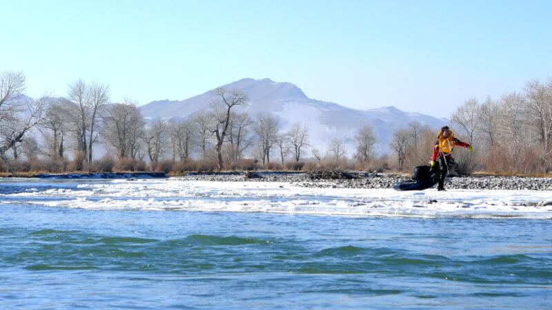 A far shot of Jamie towing his packraft on a frozen stretch of the Khovd River in Mongolia.