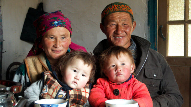 A family of four Mongolian Kazakhs pose for a photograph at the breakfast table.