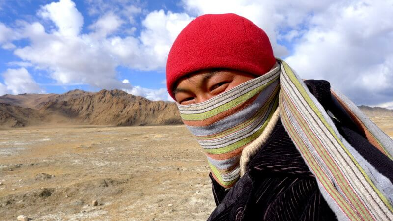 A close up photo of Alpamys wearing a red hat and colourful face scarf in western Mongolia.