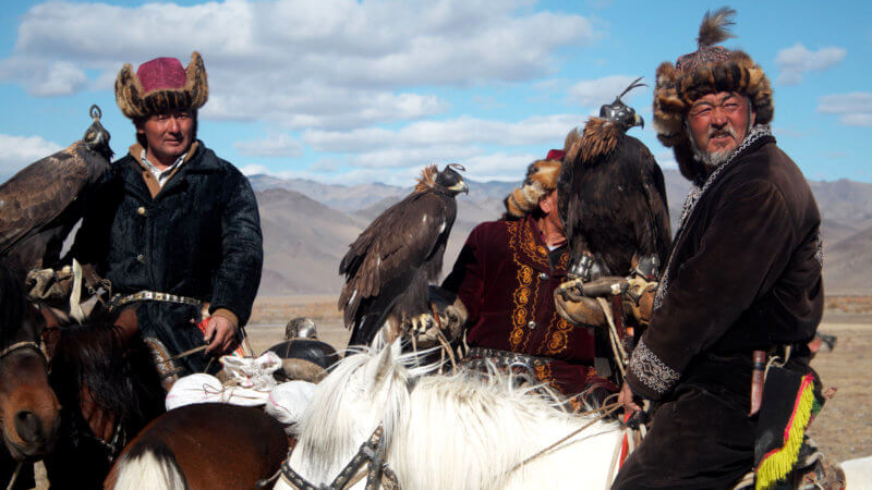 Three Kazakh eagle hunters in Western Mongolia sat on their horse and holding eagles.