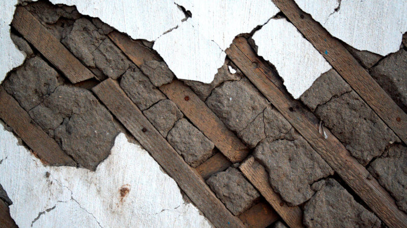 A close up photo of Mongolian house structure showing diagonal wooden beams, mud and cement.