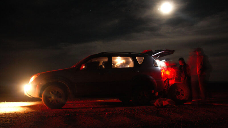 Night time photo in central Mongolia repairing a broken car tire.