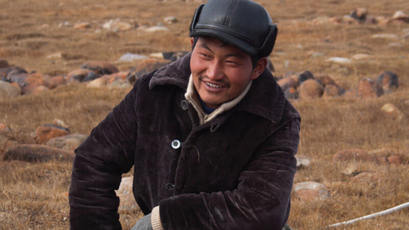 Kazakh eagle hunter crouching down and smiling as he puts a ground stake in the soil for his horse.