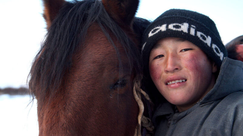 A close up photo of a Kazakh boy smiling with his cheek next to his horse.