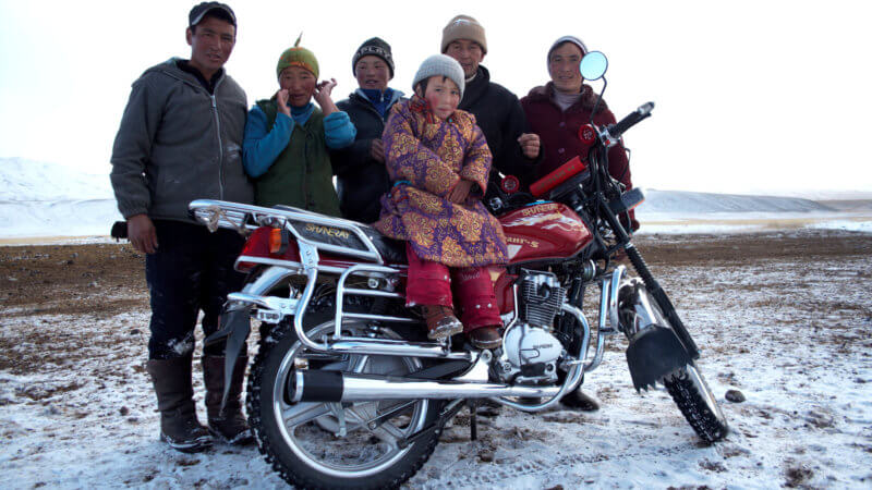 A family of six Kazakh nomads on a snowy day pose for the camera with the youngest sat on a motorcycle.