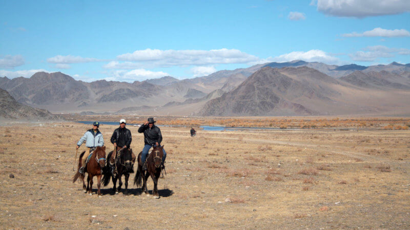 Three guys on horseback riding toward the camera with dry mountains in the background.