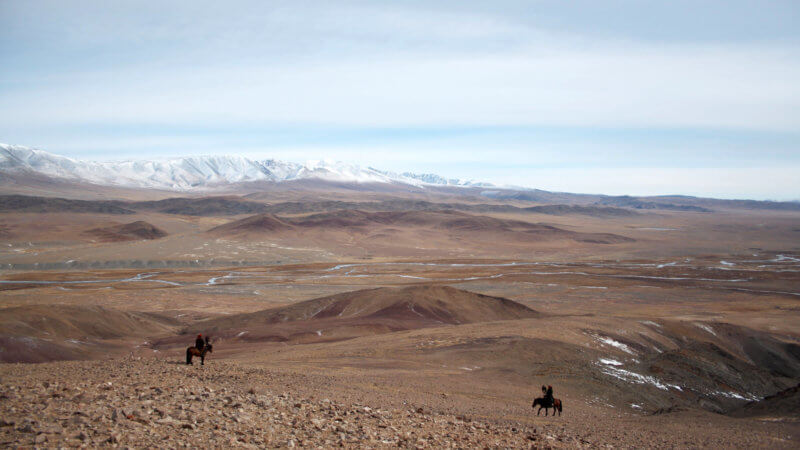 A very wide shot of a dry and cold mountain plateau with two eagle hunters at the bottom of the image.