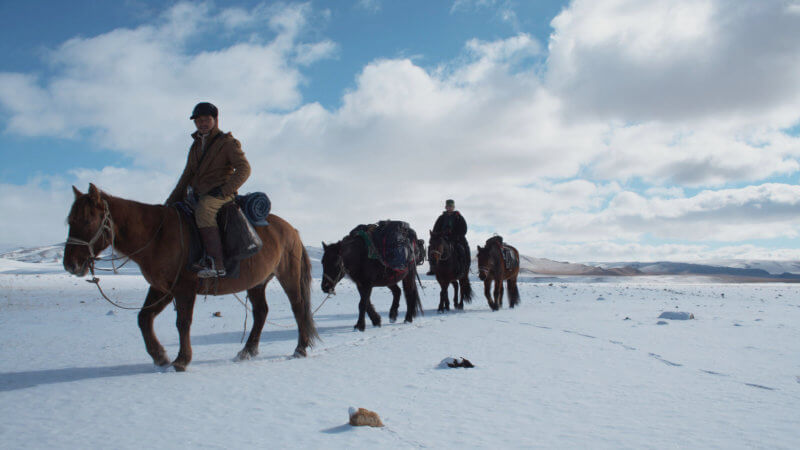 Alpamys and Jamie walking past the camera with four horses on a snow, flat part of Western Mongolia.