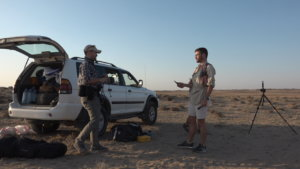 A desert runner and a photographer talk next to a jeep in a remote Kazakh desert.