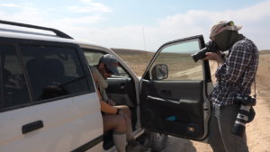 Photographer shoots Jamie whilst he is sat in the truck in a Kazakh desert.