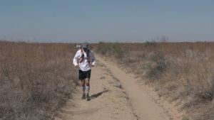 A desert runner, followed by a jeep, runs through the Saryesik-Atyrau desert in Kazakhstan.