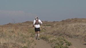 Mid-shot of desert runner Jamie running along a sandy desert track in southern Kazakhstan.