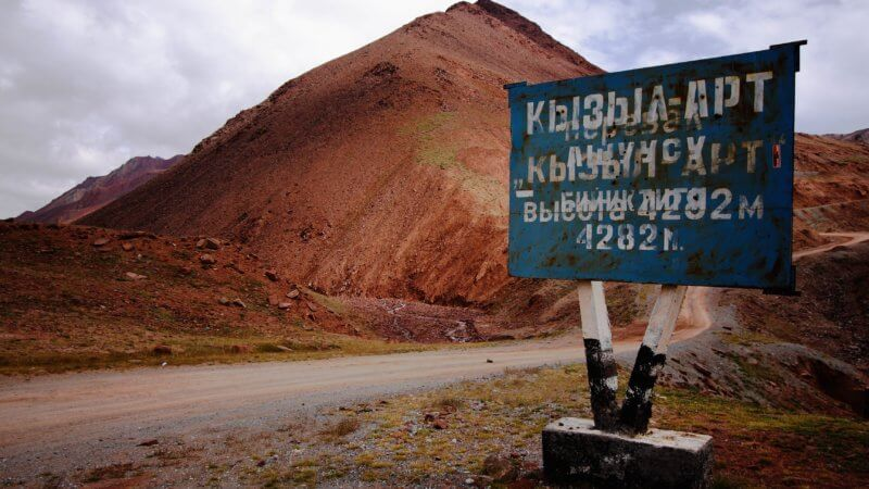 "A sign leading from Kyrgyzstan to Tajikistan reads ""Kyzyl Art Pass 4282m""."