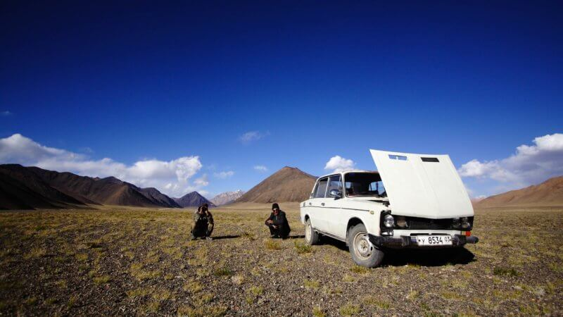 Two guys crouched beside a white Lada car in the Pamir Mountains.