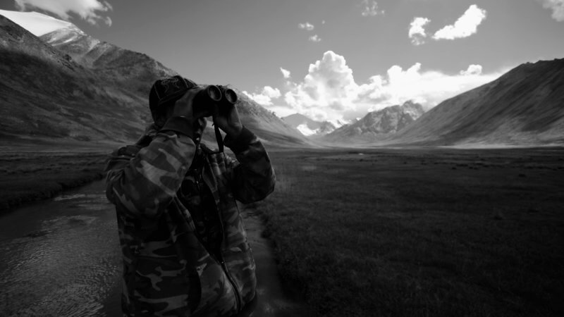 A Tajik hunter in a mountain valley looks through his binoculars.