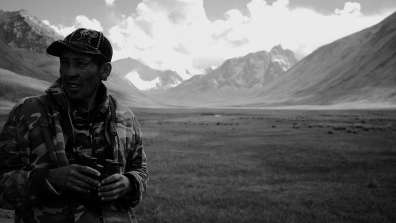 A hunter holds a pair of binoculars in his hands in between looking for Argali mountain sheep.