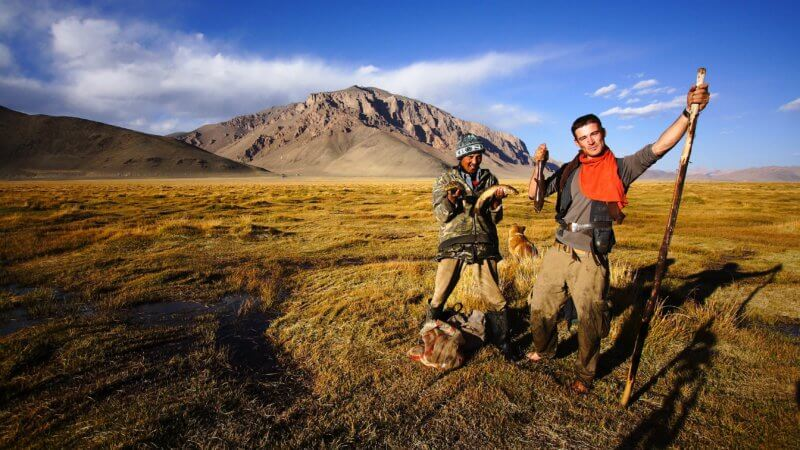 Portrait of two men fishing on a sun-kissed Pamir mountain plateau.