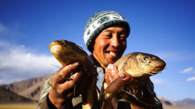 Kyrgyz fisherman smiles as he holds up two large fish caught in the Pamirs.