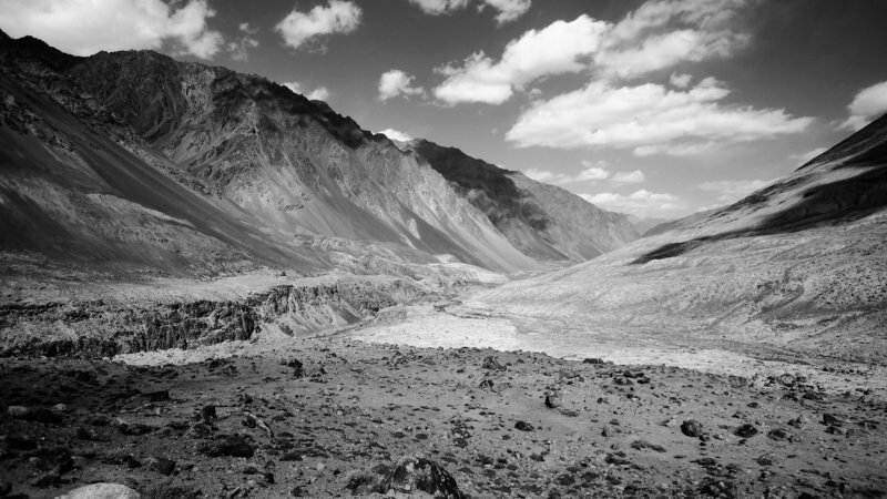 Black and white photo of a wild valley descending into the horizon towards Tajikistan's remote mountainous interior.
