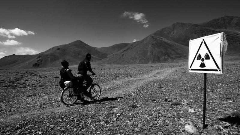 A man pedals a bike with his friend on the back as they ride past a radioactive warning sign in the Pamir Mountains.