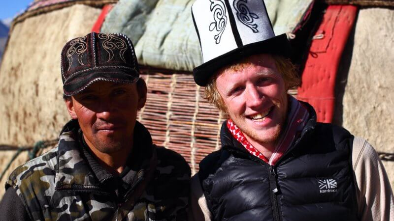 A Kyrgyz man and European tourist pose for a photo in front of a mountain yurt.