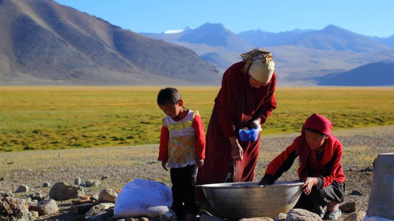 A woman and two children mix a giant bowl of flower in the open air of the Pamir Mountains.