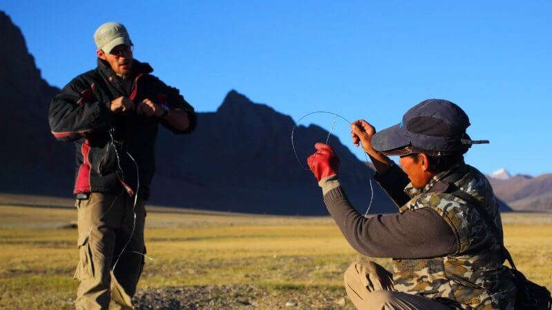 A hunter crouching on the ground demonstrates how to use a handmade wire snare trap for marmot hunting.