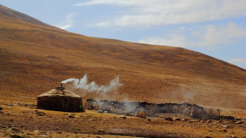 A single yurt in the dry Pamir mountains bellows smoke from its chimney.