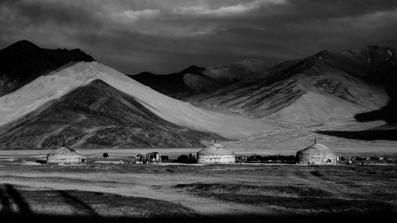 Black and white landscape photo of three yurts in front of moody, shadowy mountains.