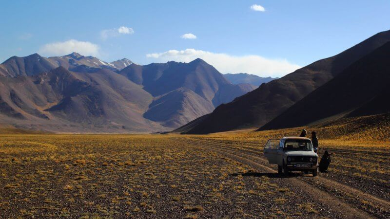 A small white Soviet-era Lada car parked on a dirt track in the Pamir Mountains.