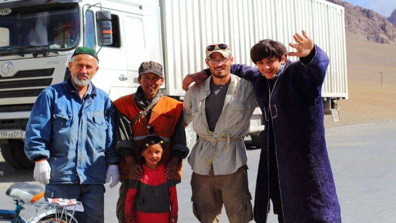Two Tajik truck drivers stand beside three others for a photo and wave.