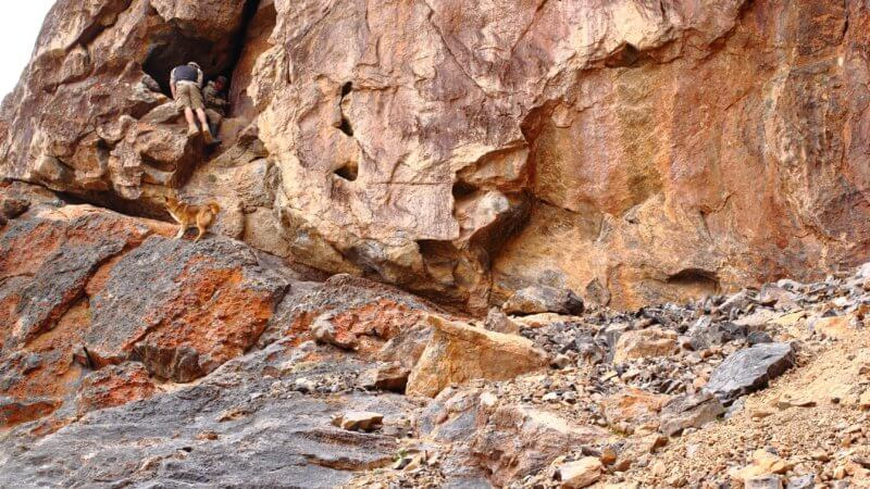 Two men scramble up into a cave system at the foot of massive cliffs in eastern Tajikistan.