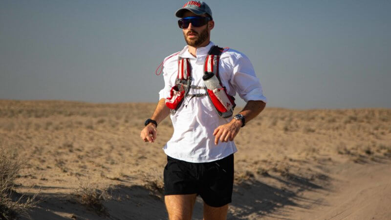 Jamie Maddison running in the Saryesik Atyrau desert wearing a Christopher Ward watch and a RailRiders shirt.