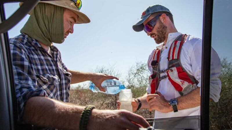 Mark Woodward replenishes Jamie's water bottle, part way through his desert run across the Saryesik-Atyrau in Kazakhstan.