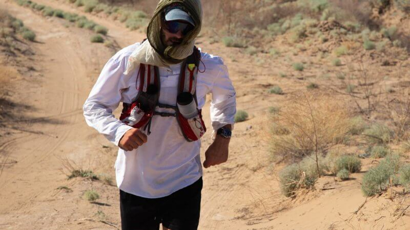 Jamie Maddison running through the Saryesik Atyrau desert wearing a RailRiders shirt and a Christopher Ward watch.