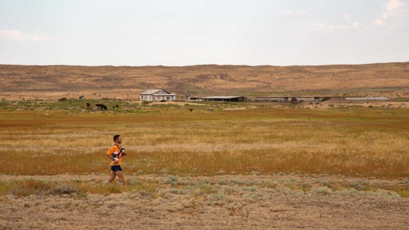 Running past a remote farmstead at the eastern edge of the Saryesik Atyrau desert in southern Kazakhstan.