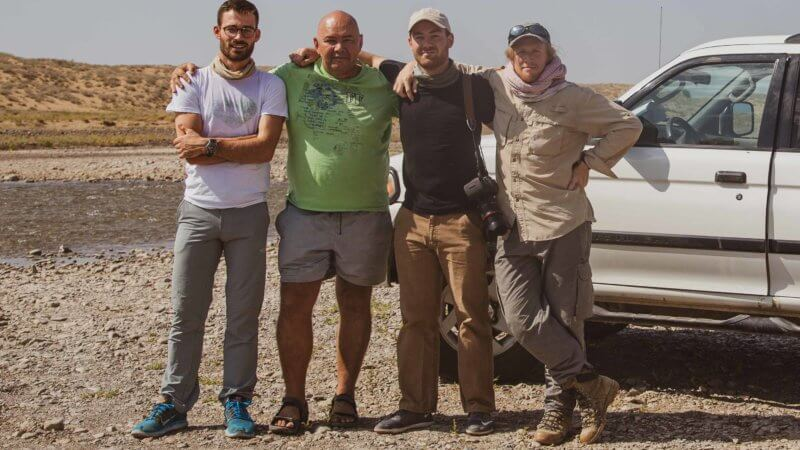 Marat, Jamie Maddison, Mark Woodward and Matthew Traver pose for a photograph beside the Karatal River, eastern edge of the Saryesik-Atyrau Desert.