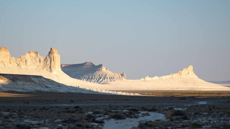 Chalk white desert mountain tops bathed in sunshine and far in the distance.
