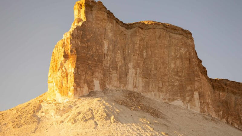 A red, orange, brown, and white coloured cliff stands above limestone desert slopes.