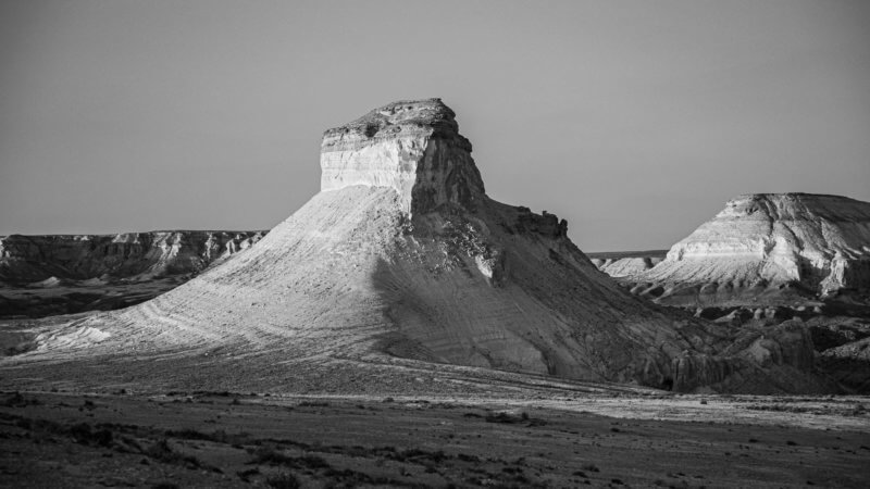 A black and white photo of a desert tower half cast in a sunset, with the other side in shadow.