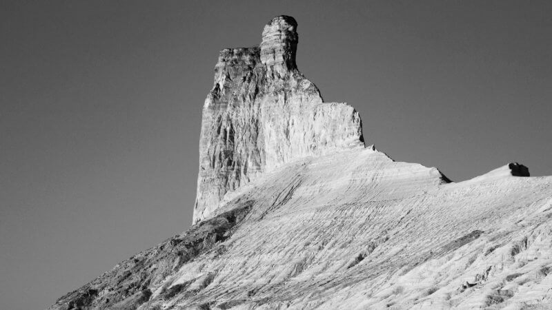 A fin-like tower of rock looms over a large, sloping cliff line.