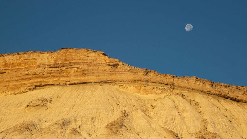 A near full moon in a blue sky hangs over orange and white stratified desert cliffs.