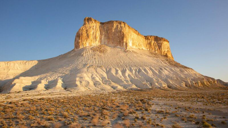 A table top, orange rock mountain sits on a sloping pile of white chalk in the Kazakh desert.