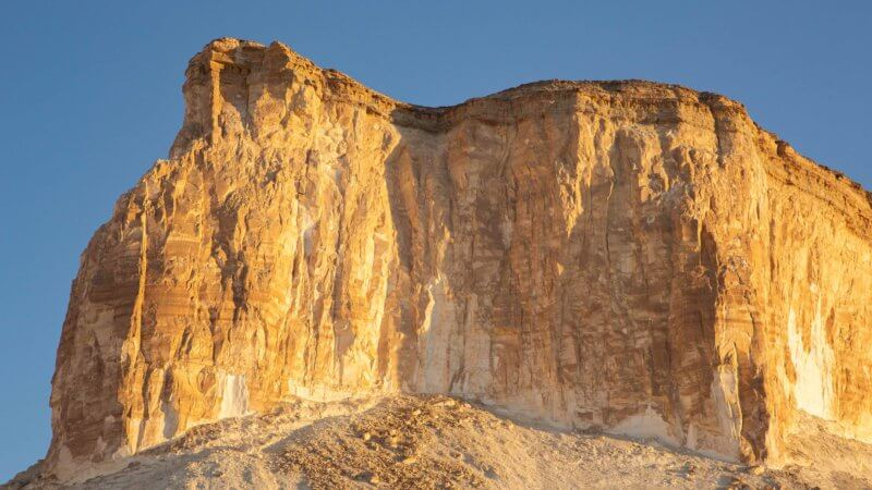 A 100 metre high cliff line shining bright orange in the sunset. Piles of rubble at the bottom of the cliff.